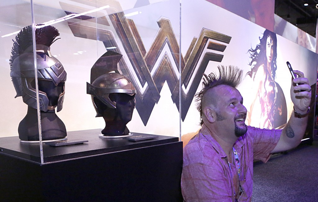 "Jim Wyatt takes a selfie next to the Queen's Guard Helmet and Amazon Army Helmet from the highly-anticipated film ""Wonder Woman"" at the Warner Bros. Consumer Products booth at Licensing Expo 2016 on Tuesday, June 21, 2016 in Las Vegas. (Photo by Bizuayehu Tesfaye/Invision for Warner Bros. Consumer Products/AP Images)"