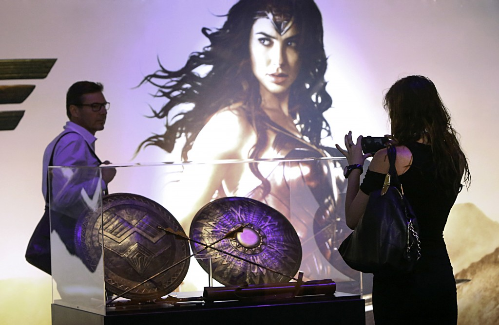 "A fan takes a picture of the Amazon Army Shield, Queen's Guard Shield, and Amazon Army Quiver and Arrows from the highly-anticipated film ""Wonder Woman"" at the Warner Bros. Consumer Products booth at Licensing Expo 2016 on Tuesday, June 21, 2016 in Las Vegas. (Photo by Bizuayehu Tesfaye/Invision for Warner Bros. Consumer Products/AP Images)"