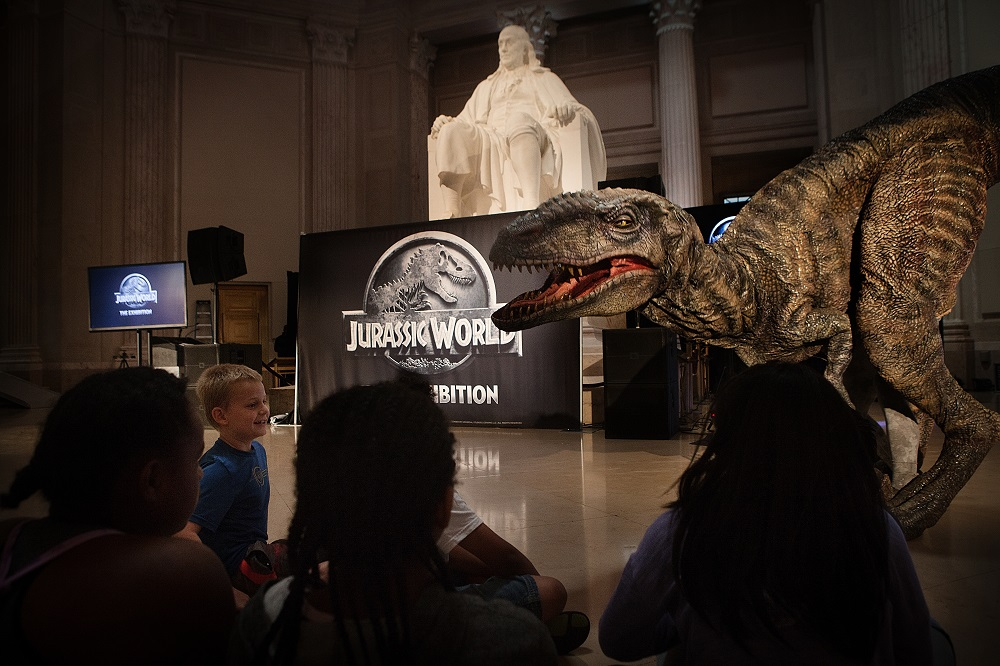 Day campers at Philadelphia's The Franklin Institute were awestruck by the arrival of a live Raptor during NBCUniversal Brand Development and Imagine Exhibitions' announcement unveiling the North American premiere of Jurassic World: The Exhibition. Bringing guests closer than ever before to real-life dinosaurs, Jurassic World: The Exhibition offers a rare look at life-size dinosaurs, set in themed environments inspired by Jurassic World, one of the largest blockbusters in cinematic history. Jurassic World: The Exhibition opens November 25, 2016 at the renowned Franklin Institute.